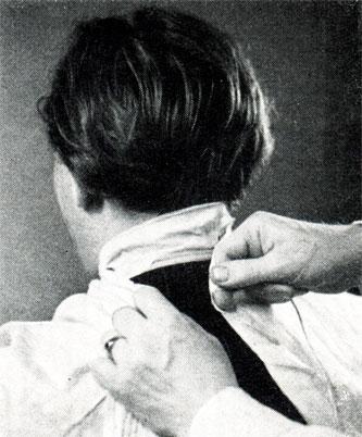 Рис. 136. Подвязывание накидки перед стрижкой